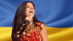 Ruslana vor der Ukrainischen Flagge. (Bildmontage) © Fahne: Fotolia, Quelle Künstler: picture-alliance / Sven Simon Foto: Fahne: Juergen Priewe, Fotograf Künstler: Sven Simon