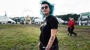 Eine Frau mit blauen Haaren und bunten Unterarm-Tattoos beim Hurricane-Festival in Scheeßel 2018 © NDR / Foto: Benjamin Hüllenkremer