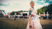 Eine Frau im weißen Kleid zeigt ihre Tattoos beim Hurricane-Festival in Scheeßel 2018 © NDR / Fotograf: Benjamin Hüllenkremer