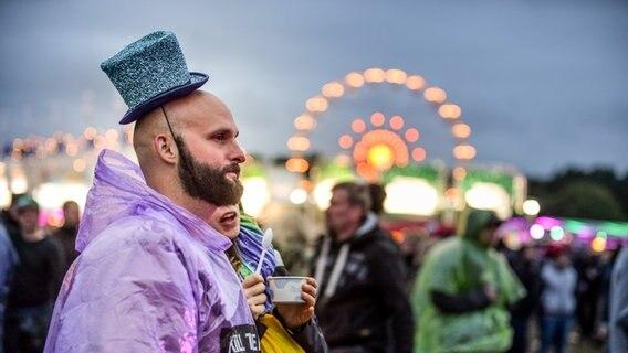 Mann mit Zylinder und Regencape beim Hurricane Festival in Scheeßel 2018. © NDR Foto: Benjamin Hüllenkremer