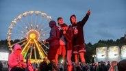 Menschen tanzen vor dem beleuchteten Riesenrad beim Hurricane Festival in Scheeßel 2018. © NDR Foto: Benjamin Hüllenkremer