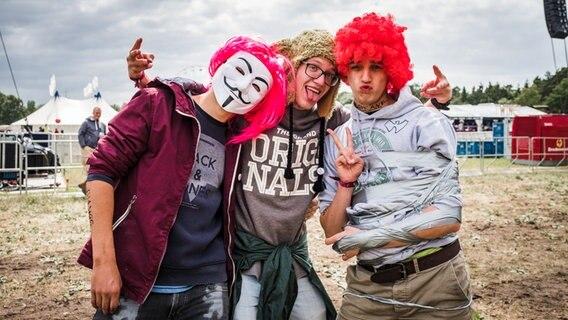 Drei Männer mit Masken und Perücken beim Hurricane Festival in Scheeßel 2018. © NDR Foto: Benjamin Hüllenkremer