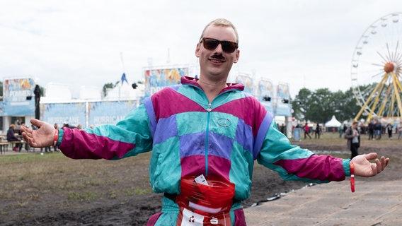 Mann mit buntem Anzug und Sonnenbrille beim Hurricane Festival in Scheeßel 2018. © NDR Foto: Benjamin Hüllenkremer