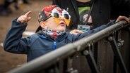 Ein Kind mit Ohrstöpseln und Eiscreme-Sonnenbrille feiert  dem Hurricane-Gelände 2018 in Scheeßel. © NDR Fotograf: Julian Rausche