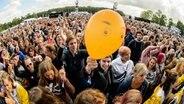 Ein Mann hält einen gelben Luftballon mit aufgemaltem Gesicht in der Hand beim Hurricane-Festival 2018 in Scheeßel. © NDR Fotograf: Benjamin Hüllenkremer
