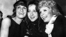 Vicky Leandros (Mitte) freut sich am 26. März 1972 in Edinburgh über ihren Sieg beim Grand Prix Eurovision de la Chanson, zusammen mit Severine (rechts) aus Monaco, der Siegerin von 1971, und der deutschen Mary Roos (links), die den dritten Platz errang. © Picture-Alliance / dpa