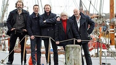 Die Mitglieder der Band Santiano auf einem Schiff: Hans Timm Hinrichsen, Axel Stosberg, Andreas Fahnert, Pete Sage und Björn Both (von links nach rechts). © dpa picture alliance Foto: Malte Christians
