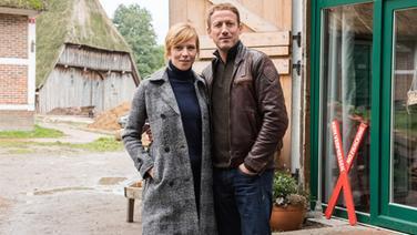 """Die Schauspieler Franzsika Weisz (links) und Wotan Wilke Möhring stehen am 19. Oktober 2016 in Hamburg während der Dreharbeiten zum Tatort """"Böser Boden"""" auf einem Bauernhof. © dpa - Bildfunk Fotograf: Daniel Bockwoldt/dpa"""