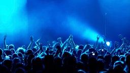 Klatschendes, stehendes Publikum in blauem Licht. © iStock Foto: dwphotos