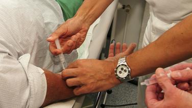 Ein Arzt gibt einem Patienten vor einer Darmuntersuchung eine Beruhigungsspritze. © picture-alliance / Okapia Foto: Klaus Rose