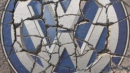 Ein auf die Straße gedrucktes, zersprungenes VW-Logo © Ralph Peters Foto: Ralph Peters