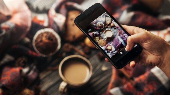 Eine Frau fotografiert mit einem Smartphone einen Weihnachtlichen Tisch mit Kuchen und Keksen. © fotolia Fotograf: sonyachny