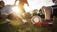 Drei junge Männer spielen im Abendlicht Fußball. © Imago/Westend61 Foto: Imago/Westend61
