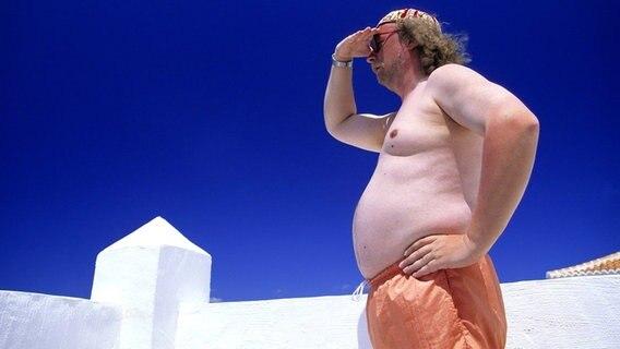 Ein Mann in Badehose und dickem Bauch steht auf der Dachterasse eines weißen Hauses und schaut wie ein Indianer in die Ferne. © Imago/blickwinkel Foto: blickwinkel