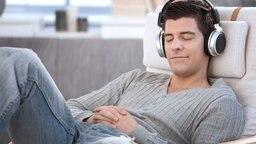 Mann liegt mit geschlossenen Augen und Kopfhörern auf dem Sofa. © Fotolia.com Foto: nyul