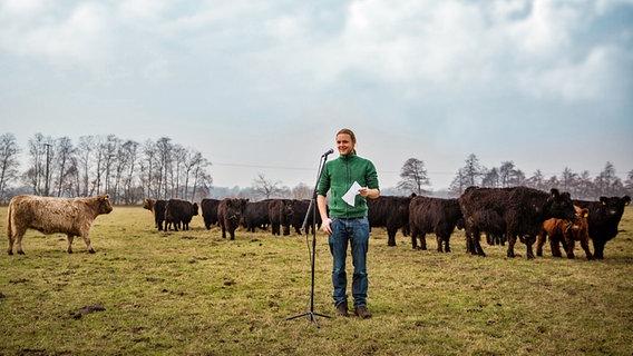 Eine junger Mann mit Pferdeschwanz steht vor einem Mikrofon auf einer Weide des Hofs Hartigswalde bei Neumünster. © Stiftung Naturschutz Schleswig-Holstein Fotograf: Jana Schmidt