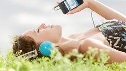 Eine Frau liegt auf einer Wiese und hört Musik. © fotolia.com Foto: Milch Images