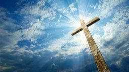 Ein Holzkreuz vor einem wolkigem Himmer. © fotolia Foto: vladischern