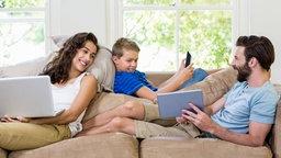 Eltern sitzen zusammen mit ihrem Sohn auf einer Couch und schauen lächeld auf ein Tablet. © WavebreakmediaMicro
