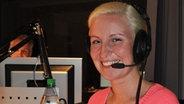 Annika Feierabend sitzt mit Kopfhörern im Hörfunkstudio © NDR Fotograf: Marta Banasch