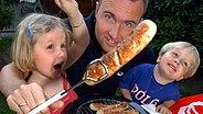Papa grillt mit den Kindern Würstchen auf einem Elektrogrill. © picture alliance