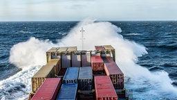 Gischt spritzt vor einem Frachter auf. © Jens Buddrich Foto: Jens Buddrich